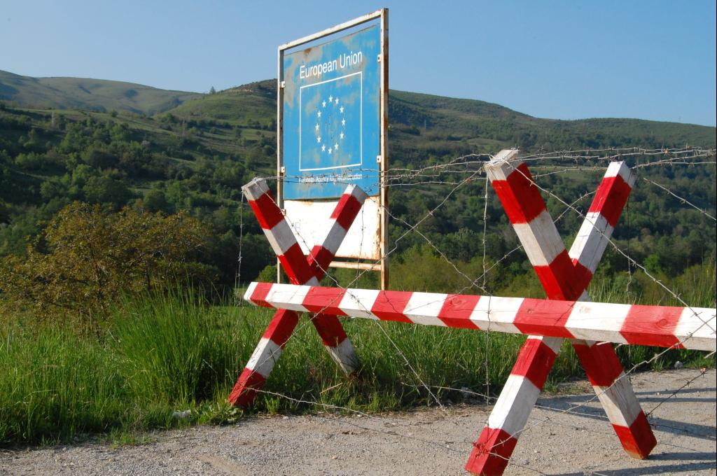 A sign that reads 'European Union' beside a road with a red and white roadblock covered in barbed wire near Štrpce, Serbia (Kosovo)
