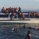 Syrian and Iraqi refugees reach the coastal waters of Lesbos in Greece, after having crossed from Turkey.